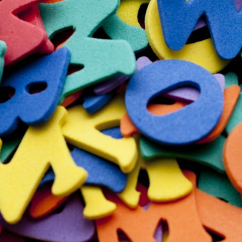 Random pile of mulitcoloured plastic alphabet letters for use in a kindergarten or preschool to teach young children basic language skills and to read, spell and write